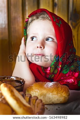 Little  girl in  Russian shawl with rolls and honey - stock photo