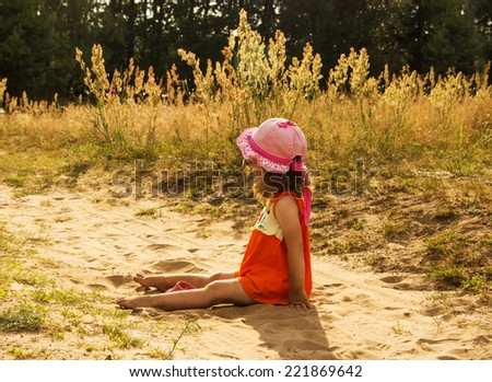 little girl is sitting on send in sunny day - stock photo