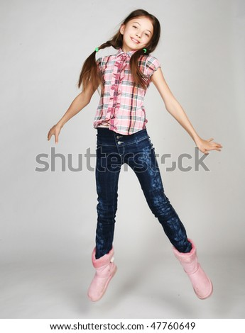 little girl jumps on a gray  background - stock photo