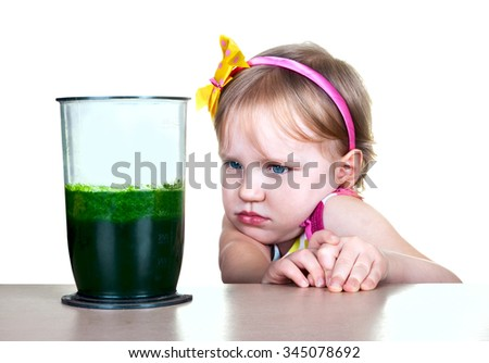 little girl near a glass of green vegetable juice smoothie. Healthy lifestyle. - stock photo