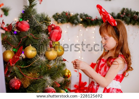 little girl near the Christmas tree, red-white concept, christmas, New Year`s decorations, illuminations - stock photo