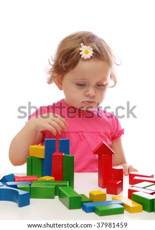 Little girl playing with colorful wooden blocks - stock photo