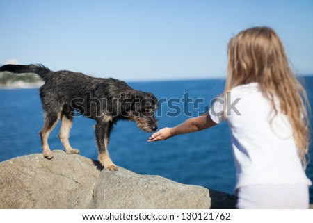 little girl playing with stray dog on sea background - stock photo