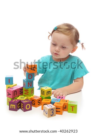 Little girl playing with wooden blocks with letters isolated on white background - stock photo