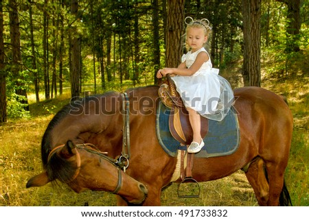 little girl riding a horse in the forest