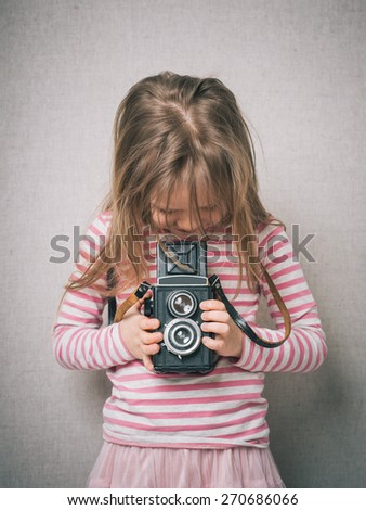 little girl shooting photo with vintage camera - stock photo