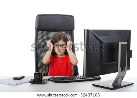 little girl wears glasses at the table in front of a computer. Isolated on white background
