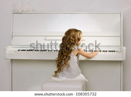 little girl with blond long curl hair in a white dress playing white piano - stock photo