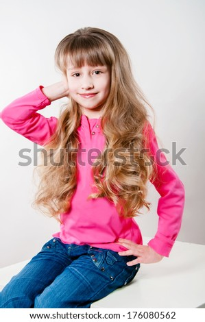 Little girl with long curly hair in a pink blouse