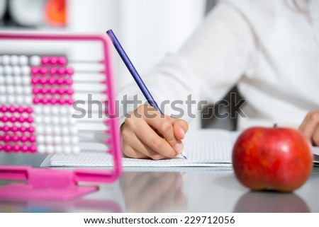 Little girl  writing in copybook, near - red apple - stock photo
