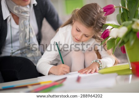 Little girl writing  while her grandmother kept, playing  together - stock photo