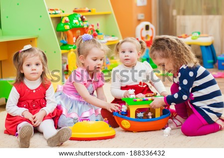 Little girls playing with toys in the playroom - stock photo