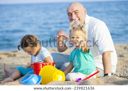 little girls with dad playing on  sea shore - stock photo