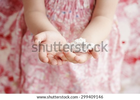 little hands of a cute girl holding stone in a heart shape ,closeup - stock photo