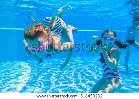 little kids deftly swim underwater in pool - stock photo