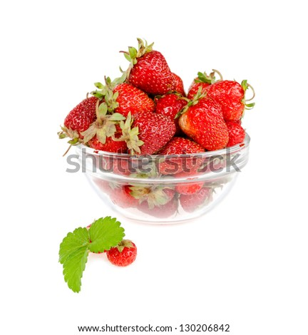 little strawberry leaves on the background of a plate with berries on a white background