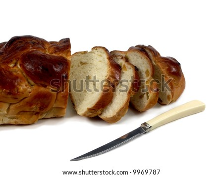Loaf of challah bread with knife isolated on white - stock photo