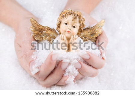 *** Local Caption *** Woman holding china angel in her palm