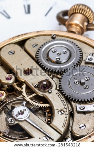 Ð¡lockwork on the background of the dial  selective focus on the pendulum with clockwork spring - stock photo