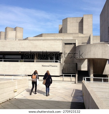 London, England - April 02, 2015: People walking by The National Theatre on the South Bank in London.A famous example of the concrete brutalist style architecture of the mid 20th century - stock photo