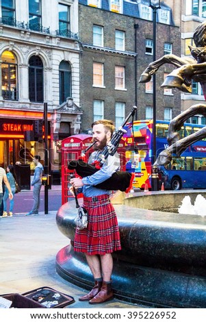 LONDON, UK - JUNE 5, 2015:  Unidentified young man with a bagpipe in the Scottish national dress at Piccadilly Circus - stock photo
