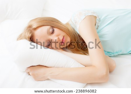 long-haired girl in nightshirt sleeping on white sheet in bed at home