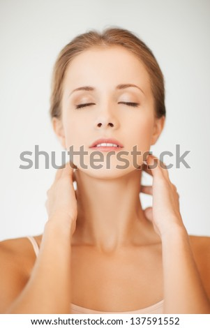 ??lose up of a young woman holding hands on her neck - stock photo