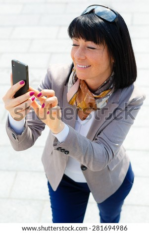 â??�°lose up portrait Happy, cheerful and smile, brunette woman, excited by what she sees on cell phone, Facial expression, reaction. Business woman sending text message from her mobile - stock photo