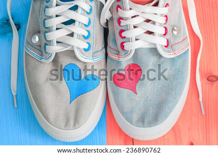 Love background with different jeans shoes and two hearts.