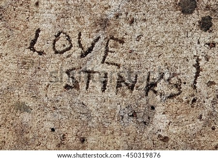 """Love Stinks!"" carved into cement, and weathered - stock photo"