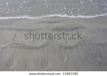 """Love"" written in the sand at the beach with the ocean water advancing over it"