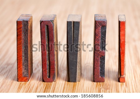 """Love"" written with colored vintage letterpress (wooden background). Soft focus! - stock photo"