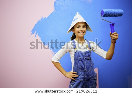 Lovely girl painting a wall in the room - Renovation of the house - stock photo