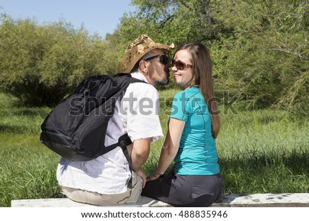 Lovers man and woman in the forest, tourists kissing on a bench