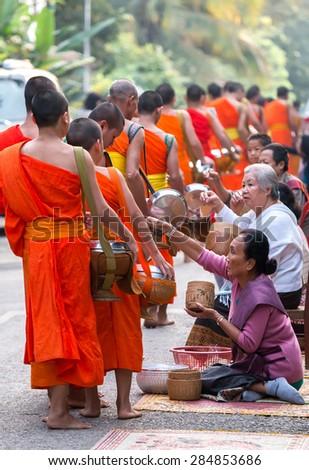 LUANG PRABANG, LAOS- APRIL 12, 2015 : Monks gathering morning alms in Luang Prabang.The tradition of giving alms to monks in Luang Prabang has been extended to tourists. - stock photo