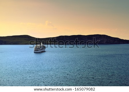 Luxury cruise ship in Navarino bay at sunset time. Cross processing from RAW file - stock photo