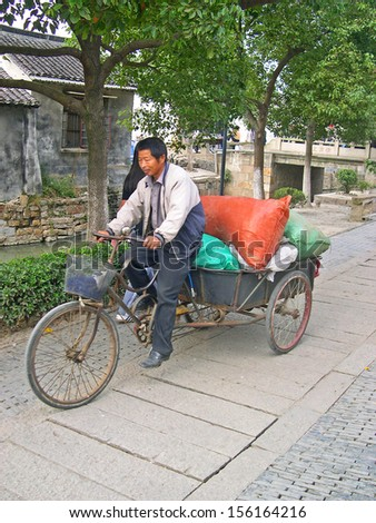 LUZHI, SHANGHAI, CHINA -Â?Â? OCTOBER 30: guy delivering goods. The ancient village is a Shanghai tourist attraction with 100000 visitors per year. October 30, 2004 Luzhi, China.