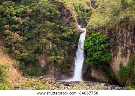 30m high waterfall near Banos Ecuador offer perfect bath place and rock climbing. - stock photo