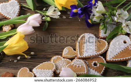 macro gingerbread heart-shaped with a yellow ribbon, flowers on wood background studio