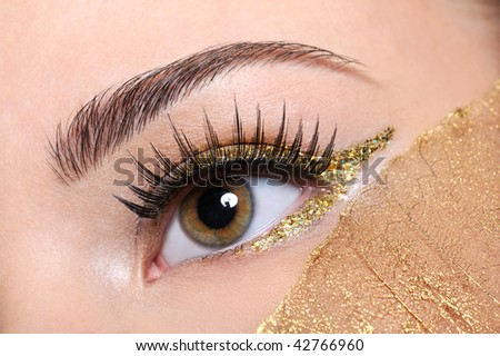 Macro shot of a woman eye with a false eyelashes and yellow, golden make-up - stock photo