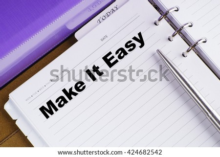 """Make It Easy"" text on notebook on a wooden table with open diary and pen - conceptual images"