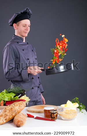 male chef tossing vegetables from wok in kitchen  - stock photo