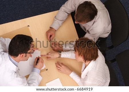 male doctor explaining diagnosis and medication to caucasian couple - stock photo