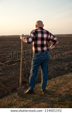 male farmer holding   shovel and looking at sky - stock photo