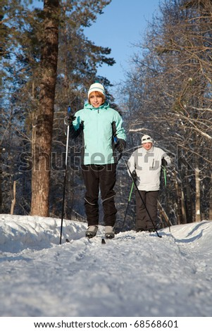 man and woman skiing in winter forest