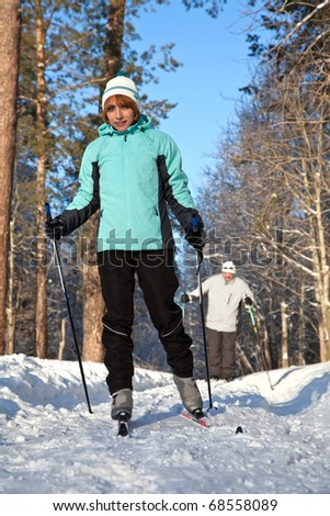 man and woman walking on ski in winter forest - stock photo
