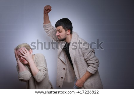 Man brandishing his wife. Husband and wife arguing, man and woman screaming. Family quarrel.  - stock photo