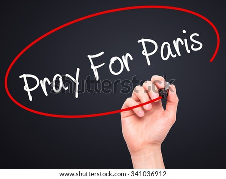 Man Hand Pray for Paris with marker on visual screen. Isolated on black.  - stock photo