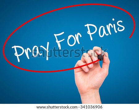 Man Hand Pray for Paris with marker on visual screen. Isolated on blue.  - stock photo