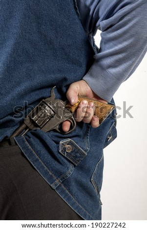 man hiding gun in back of trousers - stock photo